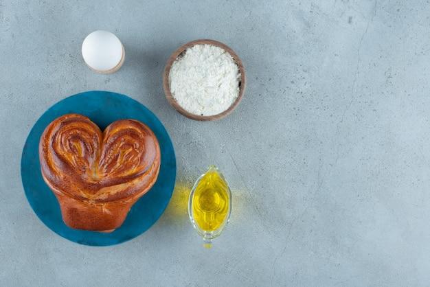 Zoet gebak, bloem en olijfolie op marmeren oppervlak.