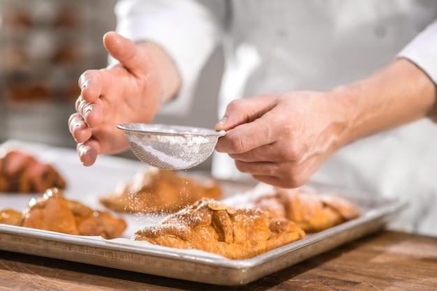 Zoet gebak, decoratie. handen van banketbakker met kleine zeef over afgewerkte gebakken goederen, oppervlak bestrooid met poedersuiker