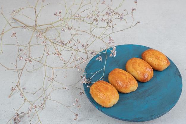 Zoet gebak met verwelkte bloem in blauw bord