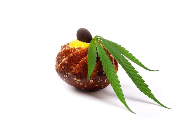 Zoet gebak met wietolie. cupcake met een blad van marihuana close-up geïsoleerd op een witte achtergrond.