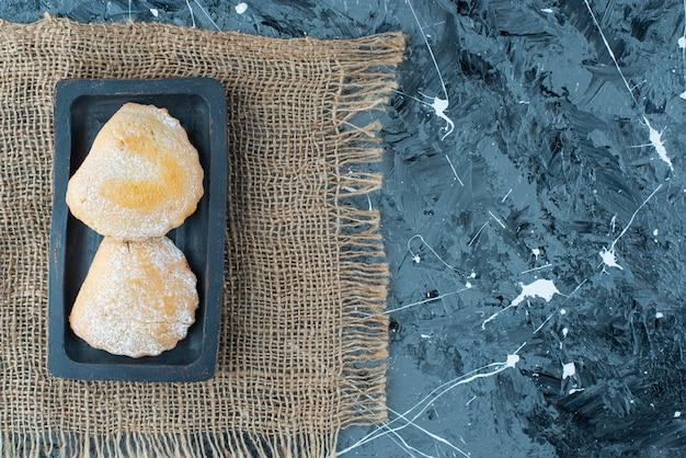 Zoet gebak op houten plaat op een textuur, op de blauwe tafel.