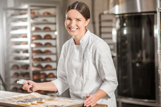 Zoet gebak. vrolijke jonge volwassen vrouw patissier in witte uniform staande in de buurt van dienblad met gebak in bakkerij