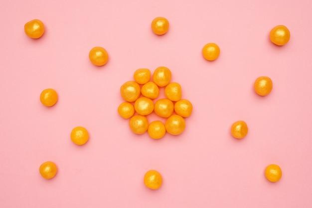 Zoet geel suikergoed op een roze, rond zoet voedsel