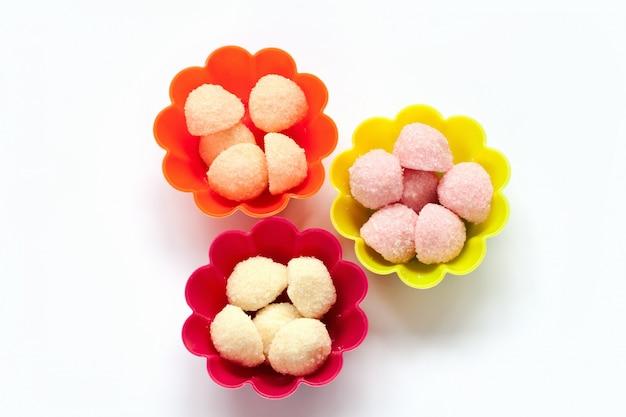 Zoet geleisuikergoed in de gevallen van de kopcake op wit