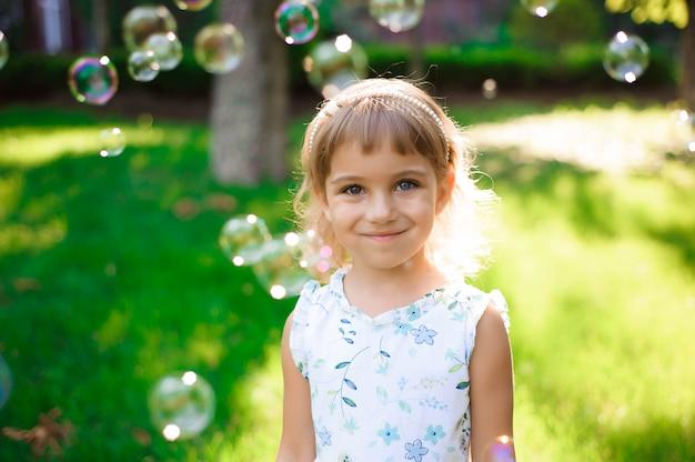 Zoet, gelukkig, glimlachend vijfjarig meisje dat op een gras legt