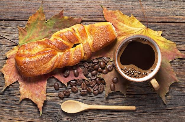 Zoet gevlochten broodje en kop warme koffie