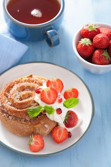 Zoet kaneelbroodje met room en aardbei als ontbijt