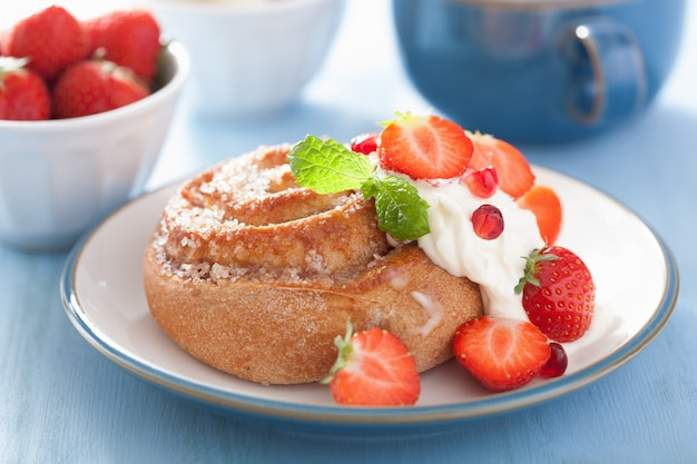 Zoet kaneelbroodje met room en aardbei voor ontbijt