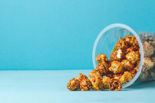 Zoet, karamelglas popcorn op een blauwe achtergrond. kopieer ruimte