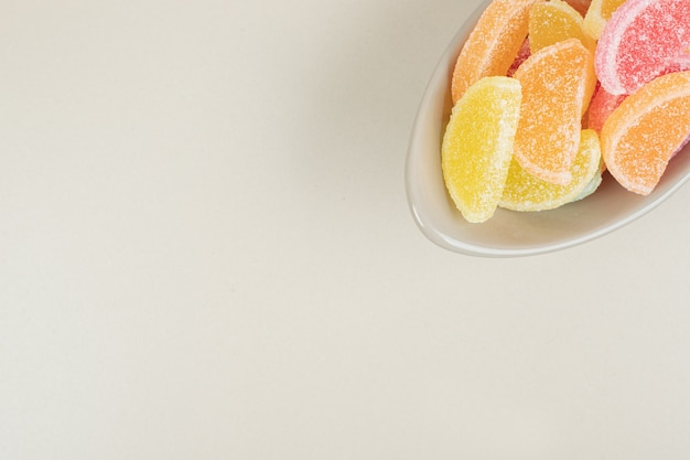 Zoet kleurrijk geleisuikergoed in kom op beige oppervlakte