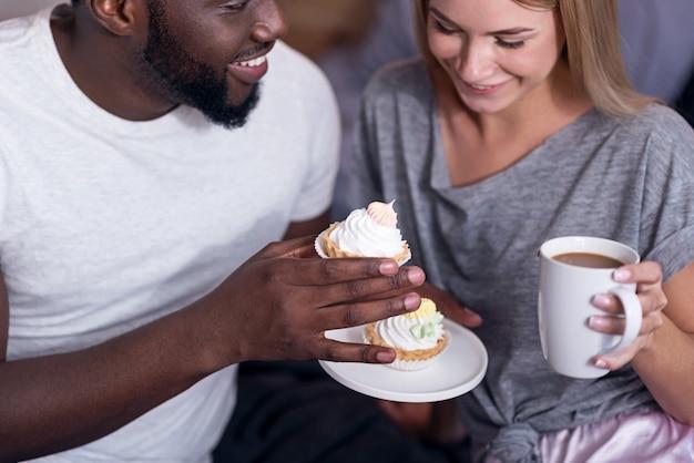 Zoet ontbijt. verrukt internationaal jong stel dat cupcakes eet en thee drinkt terwijl ze van de ochtend genieten.