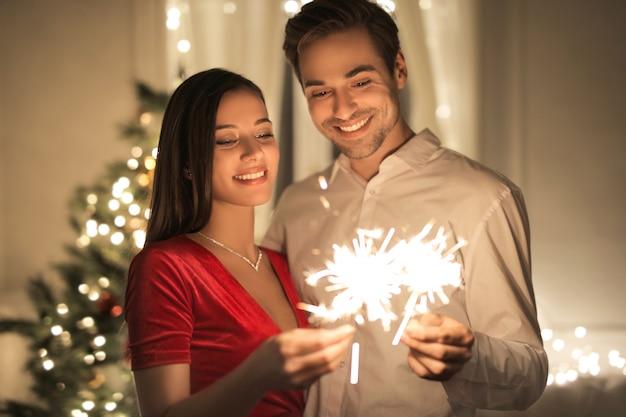 Zoet paar dat thuis knuffelt, kerstavond viert