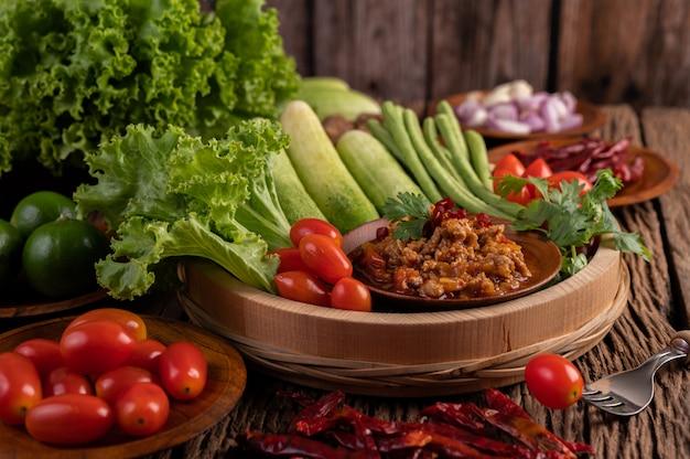 Zoet varkensvlees in een houten kom met komkommer, kouseband, tomaten en bijgerechten.
