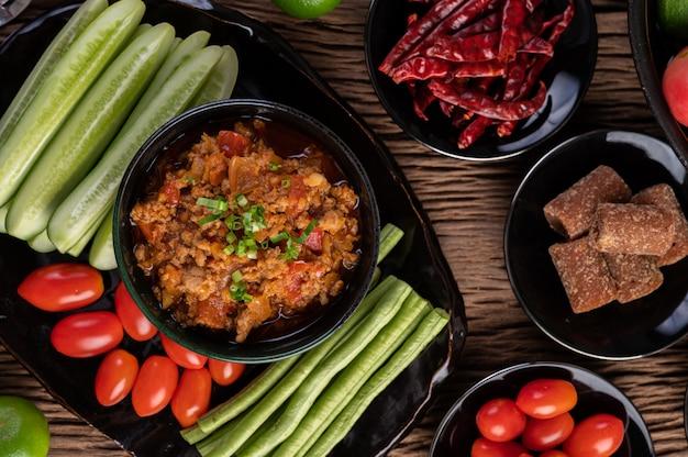 Zoet varkensvlees in een zwarte kom, compleet met komkommers, kousenband, tomaten en bijgerechten