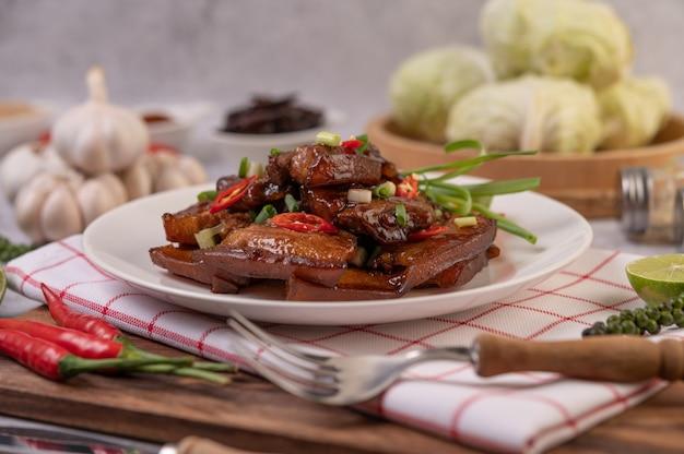 Zoet varkensvlees op een witte plaat met gehakte lente-uitjes, chili, limoen, komkommer, tomaat en knoflook.