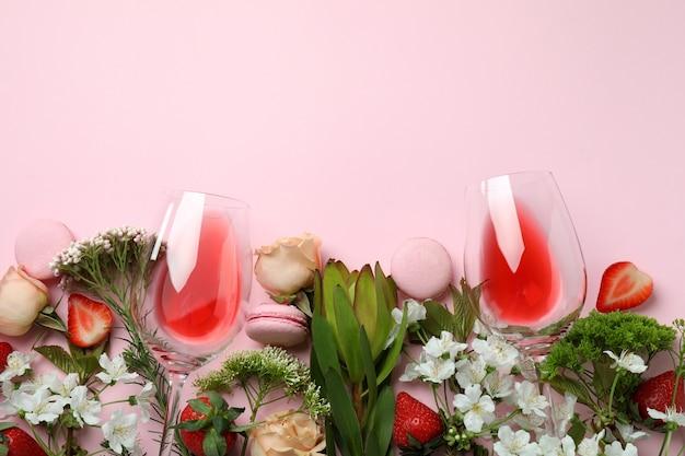 Zoet voedsel, bloemen en wijn op roze achtergrond