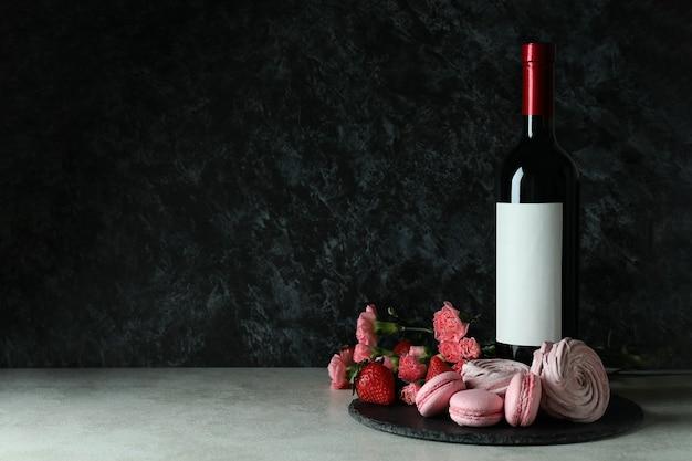Zoet voedsel en lege wijnfles tegen zwarte rokerige achtergrond