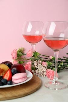 Zoet voedsel, wijn en bloemen tegen roze achtergrond
