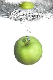 Zoet water splash op groene appel geïsoleerd op wit