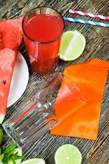 Zoet watermeloensap van watermeloenen en stukjes limoen of citroen, rood sap is een natuurlijk gezond en dieetproduct, watermeloensap met zure limoen