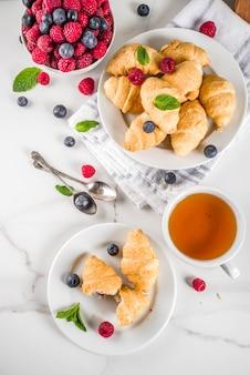 Zoet zomerdessert, zelfgemaakte gebakken mini-croissants met bessenjam, geserveerd met thee, verse frambozen, bosbessen en munt. op een witte marmeren tafel, bovenaanzicht