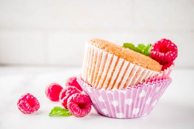 Zoet zomerdessert, zelfgemaakte gebakken muffin met frambozenjam, geserveerd met thee, verse frambozen en munt. op een witte marmeren tafel,