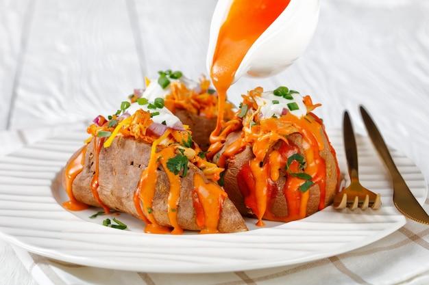 Zoete aardappel gevuld met kipfilet, cheddarkaas, koriander, lente-ui, rode ui met zure room bovenop op een witte houten tafel