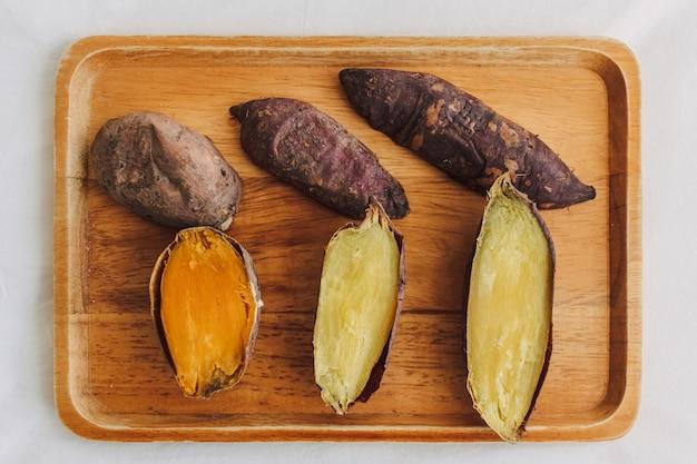 Zoete aardappel in tweeën gesneden op houten bord