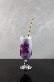 Zoete aardappel latte met ijsblokjes paarse cocktail geserveerd rietje zomers verfrissend drankje
