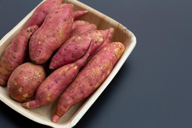 Zoete aardappel op donkere achtergrond. bovenaanzicht