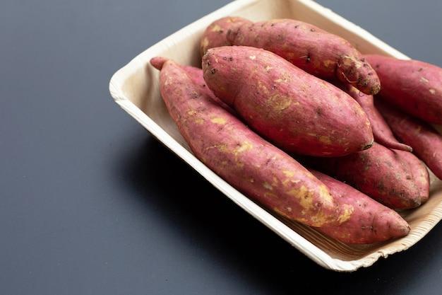 Zoete aardappel op donkere achtergrond.