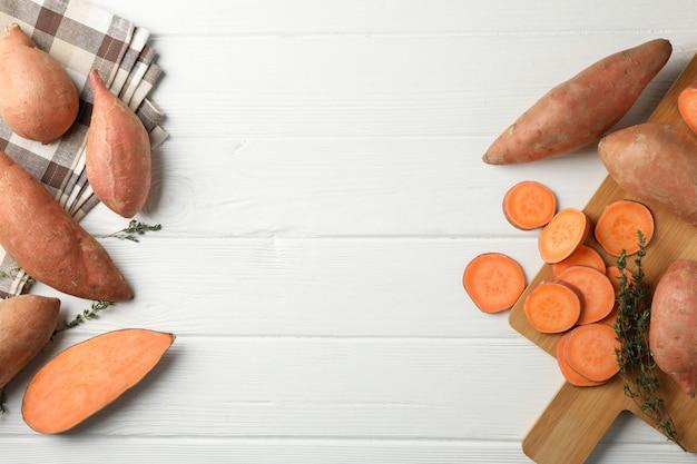 Zoete aardappelen, boord en handdoek op witte houten oppervlak