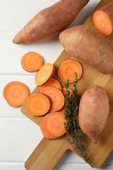 Zoete aardappelen en bord op witte houten oppervlak
