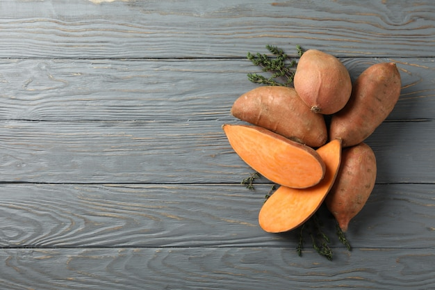 Zoete aardappelen en tijm op houten oppervlak