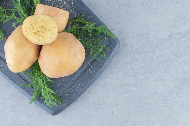 Zoete aardappelen en venkel op grijs bord.