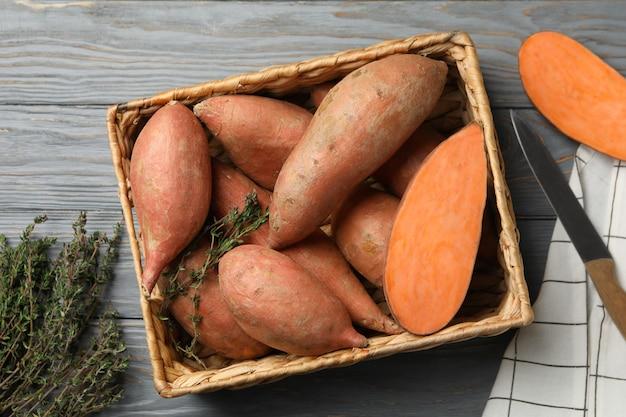 Zoete aardappelen in mand op houten oppervlak