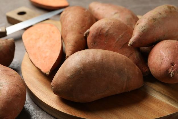 Zoete aardappelen, karton en mes op grijze ondergrond