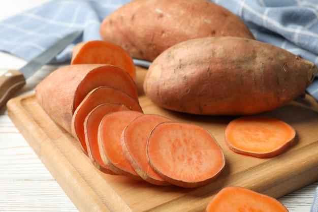 Zoete aardappelen, mes, karton en handdoek op houten oppervlak