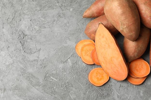Zoete aardappelen op grijze ondergrond. groenten