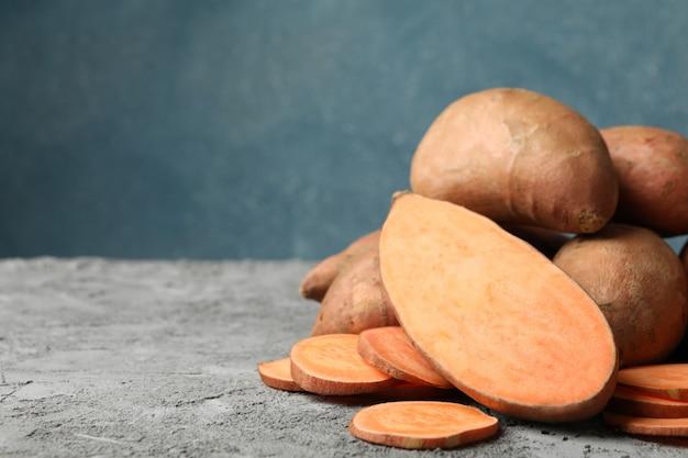 Zoete aardappelen op grijze tafel. groenten