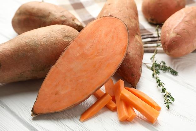 Zoete aardappelen, tijm en handdoek op witte houten oppervlak