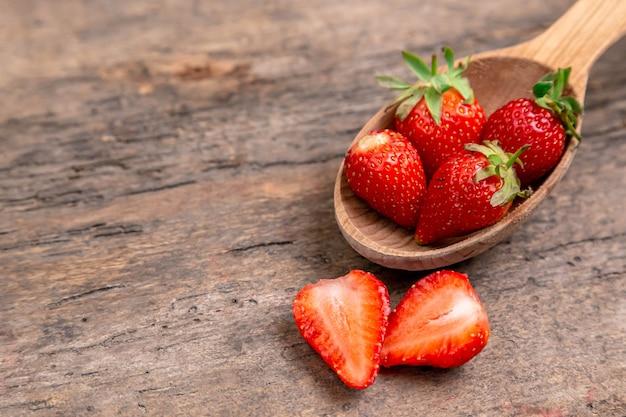 Zoete aardbei, natuurlijk fruit. aardbeien met houten lepel op houten tafel