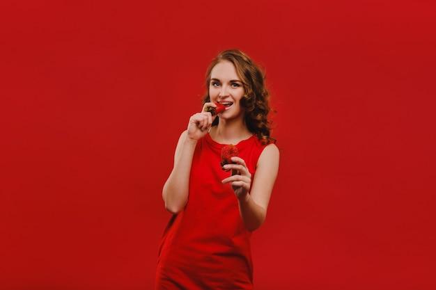 Zoete aardbeien. mooi helder meisje in retro stijl die een aardbei eet. gelukkige pin-up vrouw geïsoleerd op roze muur achtergrond eten van aardbei.