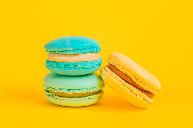 Zoete amandel kleurrijke eenhoorn blauw gele macaron of macaroon dessert taart geïsoleerd op trendy gele moderne mode achtergrond. frans zoet koekje. minimaal voedsel bakkerij concept. ruimte kopiëren