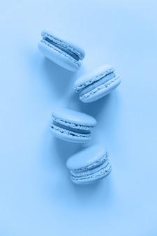 Zoete amandel macaron of macaroon dessertcake gekleurd in trendy kleur van het jaar 2020 classic blue geïsoleerd op blauwe pastel achtergrond. macro met kleur. copyspace.