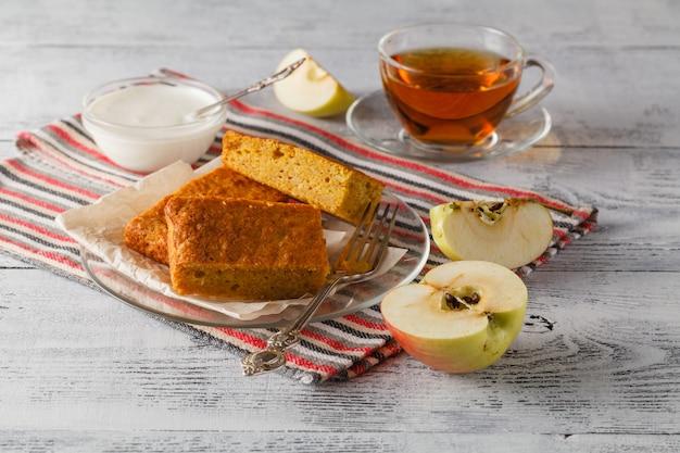 Zoete appeltaart geserveerd met appels en kopje thee op houten plaat over tafel