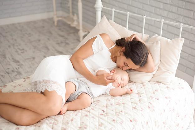 Zoete babyjongen slapen in bed met zijn moeder
