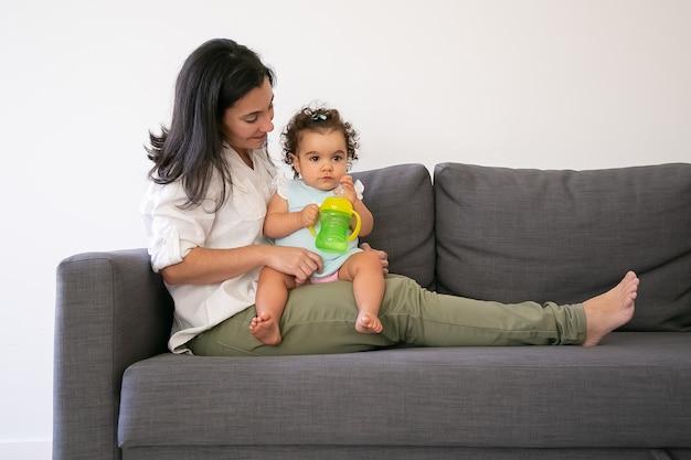 Zoete babymeisje zittend op moeders schoot en drinkwater uit de fles. kopieer ruimte. ouderschap en jeugdconcept
