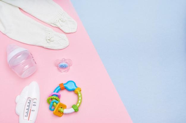 Zoete babytoebehoren op roze en blauwe achtergrond. plat leggen. bovenaanzicht kopieer ruimte.