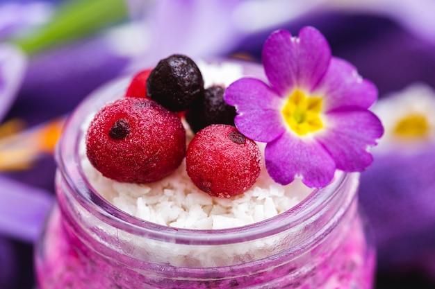 Zoete bessen en toppings van bloemen op een paarse veganistische lentesmoothie